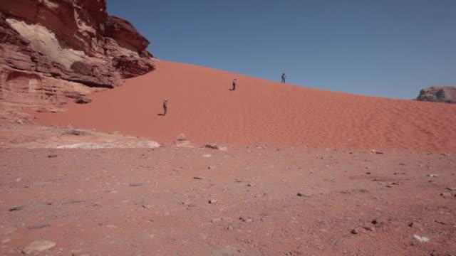Tourist walking on a sand dune in Wadi Rum desert in Jordan