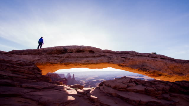 ws tourist walking on a sandstone arch - canyonlands national park stock videos & royalty-free footage