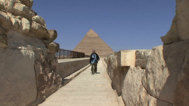 stockvideo's en b-roll-footage met ws tourist walking on path toward camera with pyramid of chephren in background, cairo, egypt - caïro