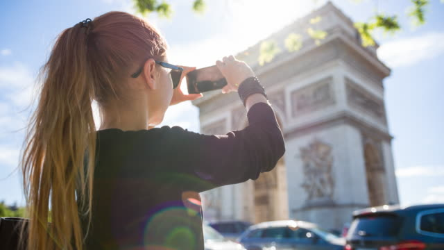 Tourist walking the streets of Paris, taking pictures of Arc de Triomphe