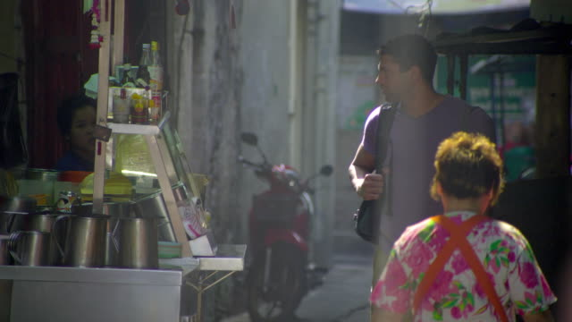 ms selective focus tourist walking through downtown alley greeting street vendor, bangkok, ayuthaya, thailand - see other clips from this shoot 1448 stock videos and b-roll footage
