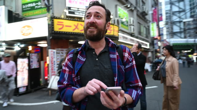tourist walking through streets of tokyo using app - tourist stock videos & royalty-free footage