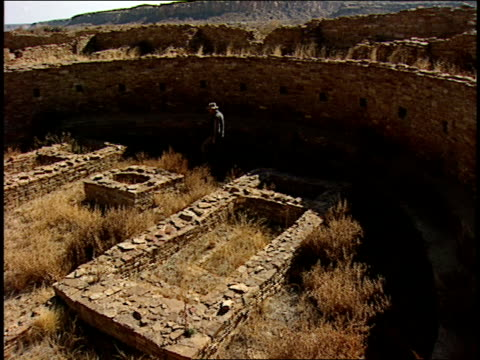 a tourist walks in the great kiva at pueblo bonito. - chaco canyon stock videos & royalty-free footage