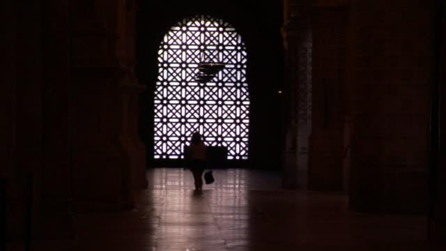 vídeos y material grabado en eventos de stock de a tourist walks through light filtered by an arched window in the moorish style. - arco característica arquitectónica