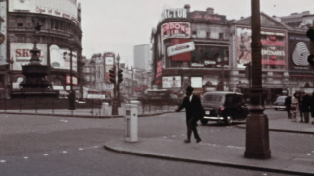 vidéos et rushes de a tourist walks through piccadilly circus in the london neighborhood of westminster. - 1960