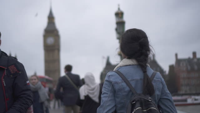 tourist walks to big ben in london - big ben stock videos & royalty-free footage