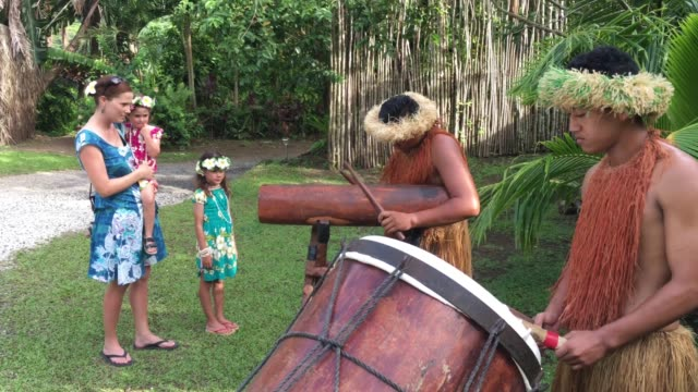 Tourist watch twoPacific Islander men plays music on a large wooden drums in Rarotonga Cook Islands