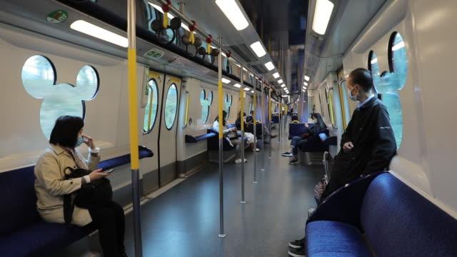 tourist wearing protective masks in disneyland train during coronavirus epidemic, hong kong, china, on monday, february 3, 2020. - public transport stock videos & royalty-free footage