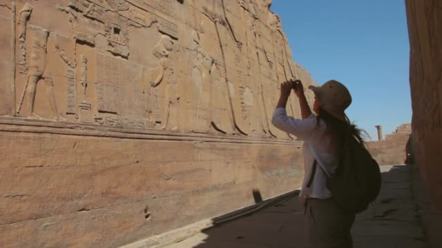 a tourist who takes pictures at the temple of kom ombo, in luxor, egypt. - egypt stock videos & royalty-free footage