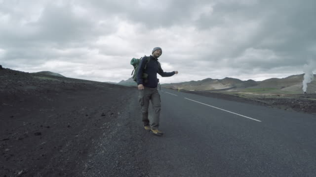 Tourist with backpack hitchhiking along a road in Icelandic desolation