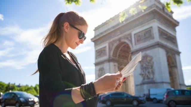 stockvideo's en b-roll-footage met toerist met de plattegrond van de stad parijs bewonderen van de triomfboog - brochure
