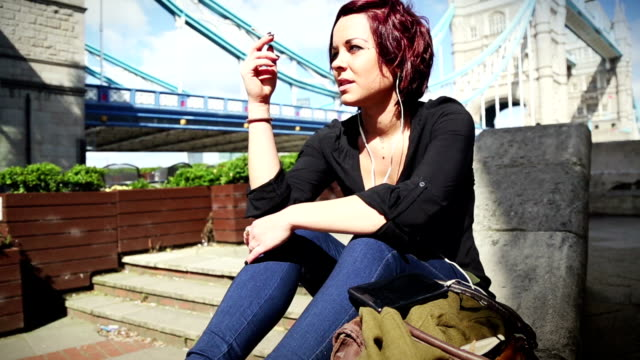 tourist woman by the tower bridge in london - cigarette stock videos & royalty-free footage