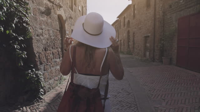 tourist woman enjoying summer vacations in italy: walking in small typical town - cappello video stock e b–roll