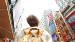 Tourist woman exploring Akihabara district in Tokyo