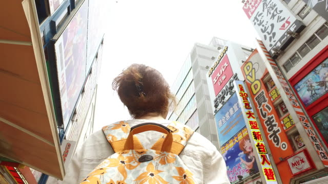 tourist woman exploring akihabara district in tokyo - scoperta video stock e b–roll