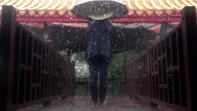 tourist woman hold umbrella in rain slow motion - standing stock videos & royalty-free footage