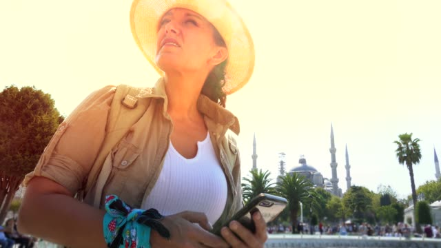 a tourist woman in istanbul speaks by phone. - spirituality stock videos & royalty-free footage