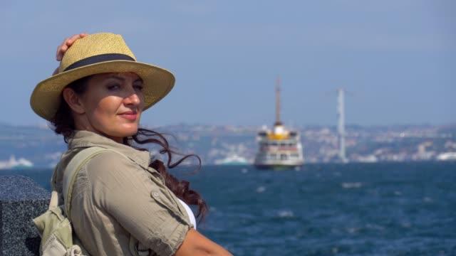 vídeos y material grabado en eventos de stock de mujer turista en la costa de eminonu en estambul. - estrecho de bósforo