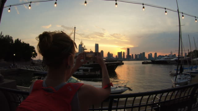 tourist woman photographing jersey city from new york with a mobile phone - marina stock videos & royalty-free footage