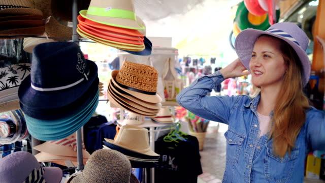 stockvideo's en b-roll-footage met toeristische vrouw winkelen op zomer vakantie - zonnehoed hoed