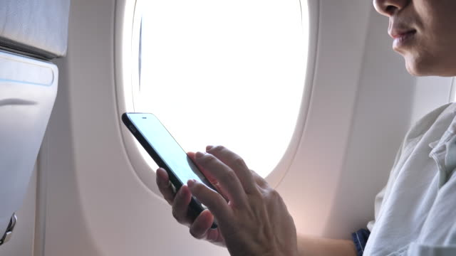 Tourist woman sitting near airplane window and using mobile phone during flight