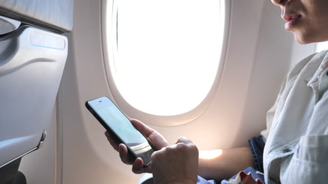Tourist woman sitting near airplane window using mobile phone during flight