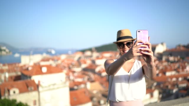 tourist woman taking a selfie at dubrovnik old town, croatia - one young woman only stock videos & royalty-free footage