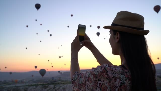 vidéos et rushes de femme touristique prenant des photos / filmant les ballons avec le smartphone pendant le lever de soleil - influenceur