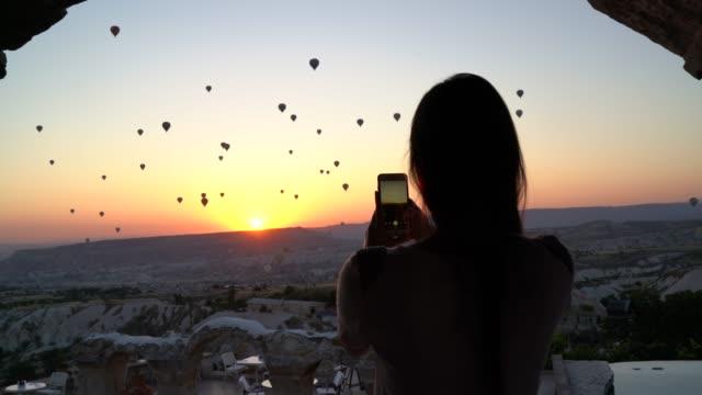 vídeos de stock, filmes e b-roll de mulher do turista que toma fotos/que filma os balões com smartphone durante o nascer do sol - capadócia