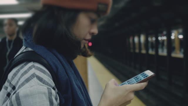 stockvideo's en b-roll-footage met toeristische vrouw met behulp van smartphone op metro platform - metro platform