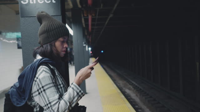 tourist woman waiting and texting with cell phones on subway platform - east asian ethnicity stock videos & royalty-free footage