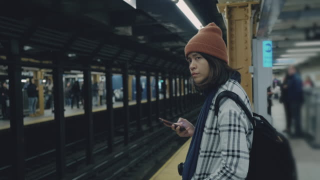 tourist woman waiting and texting with cell phones on subway platform - subway station stock videos & royalty-free footage
