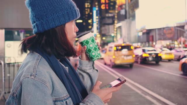 ニューヨーク市の夜にタクシーを待っているツーリストの女性 - 頭にかぶるもの点の映像素材/bロール