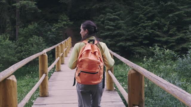 Tourist-Frau zu Fuß über die Holzbrücke