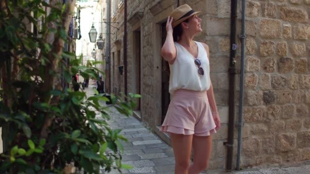 vídeos de stock, filmes e b-roll de mulher do turista que anda e que descobre a cidade velha de dubrovnik, croatia - hat