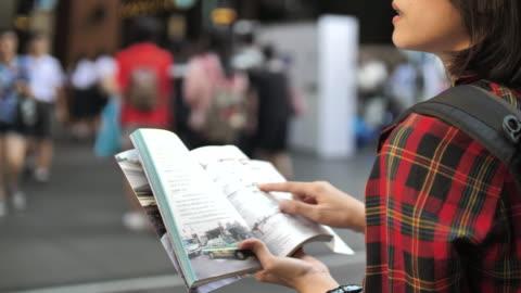 vidéos et rushes de tourisme femme marchant avec guide de carnet de voyage dans la ville - montrer la voie