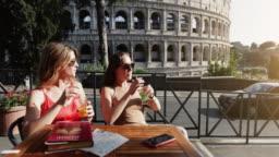 Tourist women at bar under the Coliseum of Rome