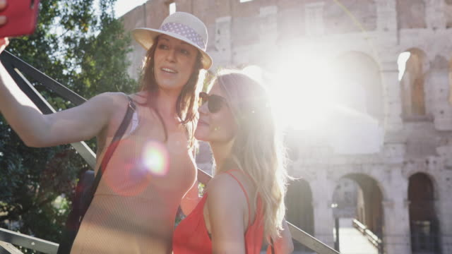tourist women in rome: selfie by the coliseum - colosseo video stock e b–roll