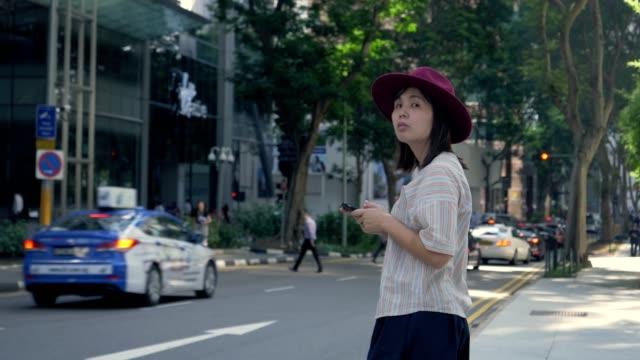 vídeos de stock e filmes b-roll de tourist women requesting and waiting uber from a smart phone in singapore city - encomendar