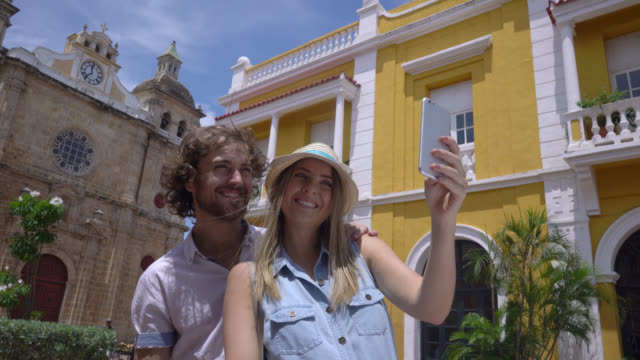 tourist young couple taking a selfie with a smartphone - colombia stock videos & royalty-free footage