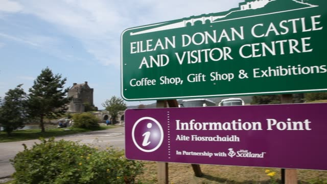 a touristic sign is announcing eilean donan castle visitor centre and information point - dornie stock-videos und b-roll-filmmaterial