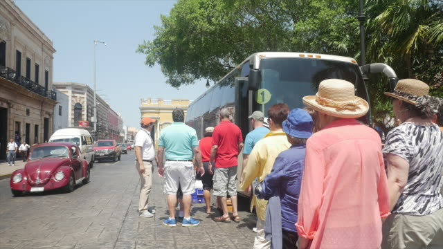 Tourists aboarding tour bus in White City of Mexico
