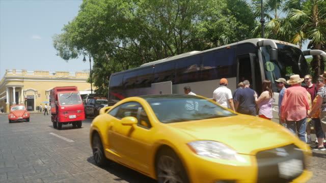 vídeos y material grabado en eventos de stock de tourists aboarding tour bus in white city of mexico - mérida méxico