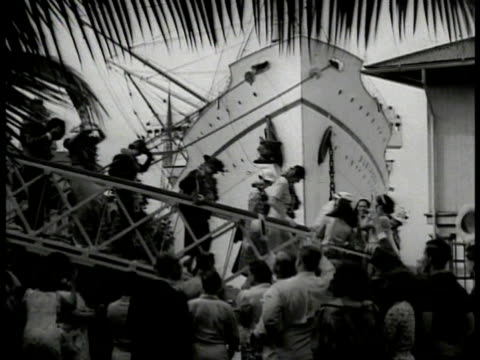 vidéos et rushes de tourists across gangplank, ship in dock bg. tourists being greeted by hawaiian women, receiving leis. night: girls performing hula dance, band bg.... - îles hawaï
