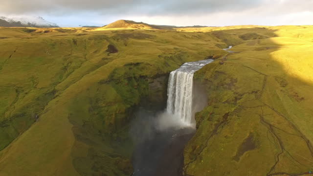 AERIAL Tourists admiring Skogafoss waterfall in Iceland