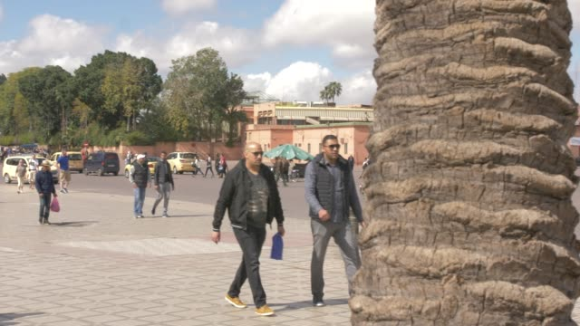tourists and activity on djemaa el fna showing koutoubia minaret, marrakech, morocco, north africa, africa - arbeitstier stock-videos und b-roll-filmmaterial