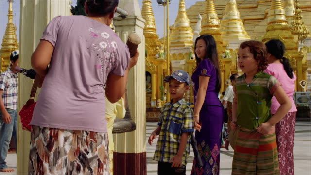 tourists and devotees ring the bell at shwedagon zedi daw (shwedagon pagoda) in yangon - speeded up. - newly industrialized country stock videos and b-roll footage