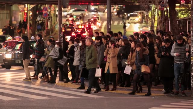 tourists and japanese commuters crossing the road at shibuya crossing. foreign tourirsts take advantage of japanese yen's falling value on february... - segnale per macchine e pedoni video stock e b–roll