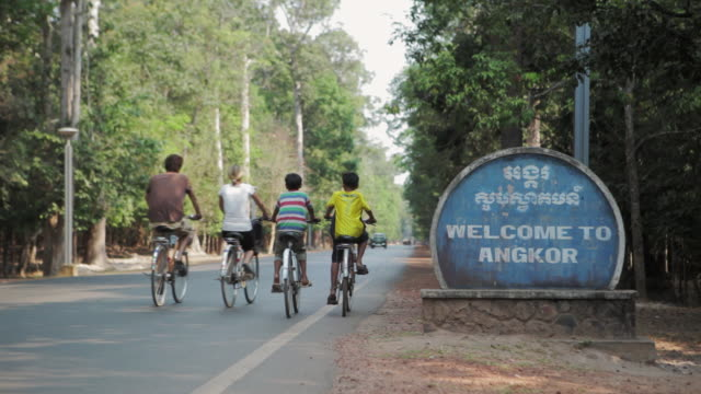 ls tourists and local children cycle past angkor wat temples entrance sign / siem reap, cambodia - entrance sign stock videos & royalty-free footage