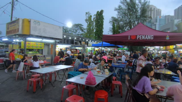 tourists and locals are having their meal at the food stall in the evening. - market stall stock videos & royalty-free footage